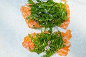 foto of rocket salad  - fresh salmon carpaccio sushi sashimi with arugula rocket salad and caper on top - JPG
