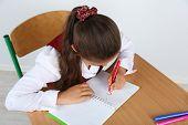 pic of schoolgirls  - Beautiful little schoolgirl in classroom and draws in notebook - JPG