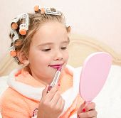 stock photo of hair curlers  - Cute little girl with lipstick and mirror and hair curlers - JPG