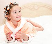 stock photo of hair curlers  - Happy funny little girl with manicure and hair curlers in bathrobe lying on bed - JPG