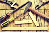 foto of pliers  - Hammer flat file pliers screwdriver monkey wrench screws boards and blade on natural wooden background - JPG