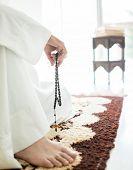 image of arab man  - Arabic aged man sitting on ground using traditional beads - JPG