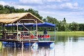 stock photo of raft  - Motorized water tourism raft moored at the wooden small pier in the water body - JPG