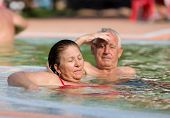 foto of hot couple  - Senior couple enjoying sun and holiday in the pool with hot water - JPG