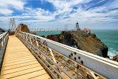 stock photo of lighthouse  - The bridge to Lighthouse on the rock under beautiful sky - JPG