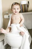 stock photo of disobedient  - A Toddler ripping up toilet paper in bathroom - JPG