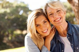 stock photo of retirement age  - happy middle aged blond mother and adult daughter outdoors - JPG