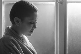 pic of hospital gown  - Young cancer patient standing in front of hospital window - JPG