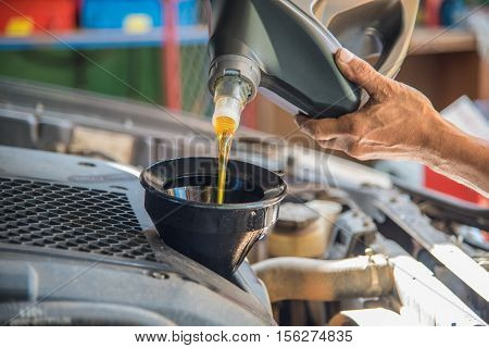 poster of Car maintenance servicing mechanic pouring new oil lubricant into the car engine, A mechanic pours fresh oil into a car engine as part of its maintenance