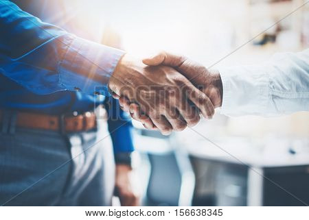 Close up view of business partnership handshake.Concept two businessman handshaking process.Successful deal after great meeting.Horizontal, flare effect, blurred background