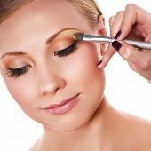 foto of makeup artist  - Makeup artist applying yellow eyeshadow - JPG