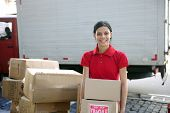 picture of movers  - young delivery courier or mover delivering cardboards - JPG