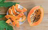 Ripe Papaya On Wood Table From Above , Ripe Papaya Health Benefits. poster