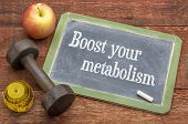 Boost your metabolism concept -  slate blackboard sign against weathered red painted barn wood with  poster