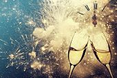 Glasses with champagne against fireworks and clock close to midnight - New Year, holiday background poster