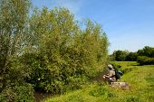 foto of bagpack  - Man is resting near the river in nature landscape - JPG
