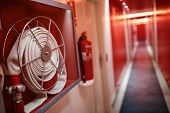 Fire extinguisher and fire hose reel in hotel corridor poster