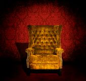 foto of grommets  - A grungy gold velvet chair in a dark room with red Victorian wallpaper - JPG