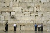 men praying next to the wailing wall, jerusalem,israel