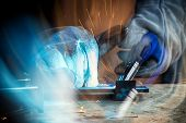 Strong Man Welder In Work Clothes Hard Working And Welds With A Welding Machine Metal   In The Works poster