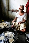 DELHI - FEBRUARY 26: Man cooking chapatis in oil to make Puri on February 26, 2008 in Dehli, India.