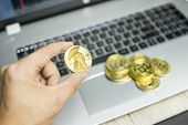 Male Businessman Hand Holding Tree Titan Bitcoin On A Background Of Laptop Keyboard And Pile Of Gold poster