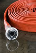 stock photo of firehose  - A rolled up firehose on the floor in a firestation used by firefighters