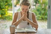 Christian Worship And Praise. A Young Woman Is Reading The Bible And Praying In The Early Morning poster