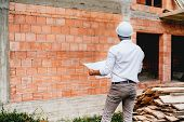 Construction Engineer With Plans, Working On Building Construction Site. Brick Walls, Infrastructure poster