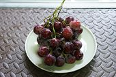 Bunches Of Fresh Ripe Red Grapes On The Dish. Ancient Style, A Beautiful Background With A Branch Of poster