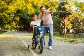Happy father and his son having fun together at the green park, teaching son how to ride a bicycle,  poster
