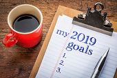 my 2019 goals list on clipboard and coffee against grunge wood desk poster