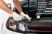 Cropped Image Of Auto Mechanic Auto Mechanic Repairing Car With Wrench On White poster