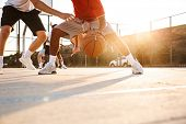Cropped image of strong multiethnic men basketball players playing basketball at the sport ground poster