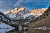 Maroon Bells and Maroon Lake with reflection of rocks and mountains in snow around at autumn in Colo poster