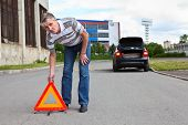 Mature Man Sets Triangle Warning Sign On Road And Going To Car With Blinker Lights On Wayside
