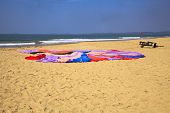 picture of boggy  - Generic horizontal beach and ocean landscape of a parachute laid flat on the sandy Uttorda Beach at Goa drying in the hot Indian sun - JPG