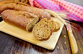 Rye Baguettes With A Knife And A Wicker Basket