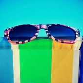 a pair of sunglasses on a colorful deckchair on the beach