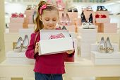 image of shoe-box  - Little girl stands and holds open box with pink shoes in shoe store - JPG