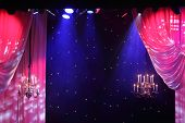 Curtains with pink lighting and chandeliers hanging in theater.
