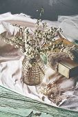 stock photo of keepsake  - Spring white flower branches on grunge table with silk cloth and a book with lace and pearl wedding keepsakes - JPG