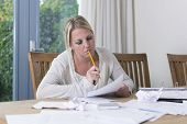 stock photo of middle class  - Woman going through unpaid bills - JPG