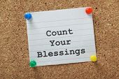 stock photo of blessed  - The phrase Count Your Blessings typed on a piece of lined paper and pinned to a cork notice board - JPG