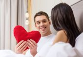 hotel, travel, relationships, holidays and happiness concept - smiling couple in bed with red heart-