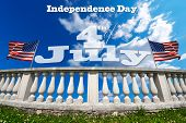 stock photo of balustrade  - White stone balustrade with two US flags on blue sky with clouds and phrase  - JPG