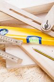 stock photo of joinery  - Close up view of a colorful yellow carpenters level ruler and right angle lying on planks of new hardwood together with a pencil for measurements in a carpentry construction DIY and joinery concept - JPG