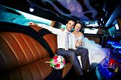 picture of limousine  - Bride and groom in wedding limousine with glasses of champagne - JPG