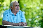 stock photo of muse  - Elderly man sitting in the garden at a wooden table thinking and staring into the distances as he reminisces fond memories with copyspace - JPG