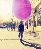 image of helium  -  little boy running with a balloon done with a retro vintage instagram filter  - JPG